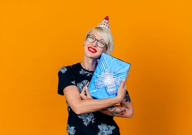 Улыбающаяся молодая белокурая тусовщица в очках и кепке на день рождения держит подарочную коробку, глядя в камеру, изолированную на оранжевом фоне с копией пространства