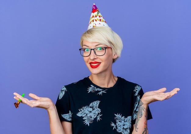 보라색 배경에 고립 된 빈 손을 보여주는 카메라를보고 파티 송풍기를 들고 안경과 생일 모자를 쓰고 웃는 젊은 금발 파티 소녀