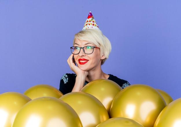 Улыбающаяся молодая белокурая тусовщица в очках и кепке дня рождения стоит за воздушными шарами, положив руку под подбородок, глядя в сторону, изолированную на фиолетовом фоне