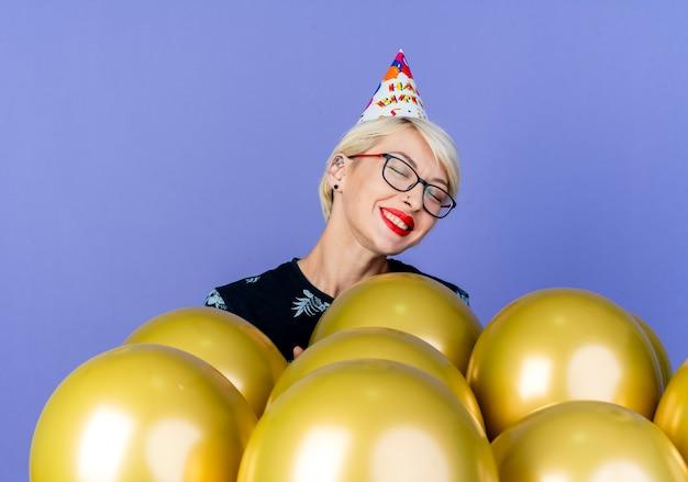 Улыбающаяся молодая блондинка вечеринка в очках и кепке дня рождения, стоящая за воздушными шарами с закрытыми глазами, изолированными на фиолетовом фоне