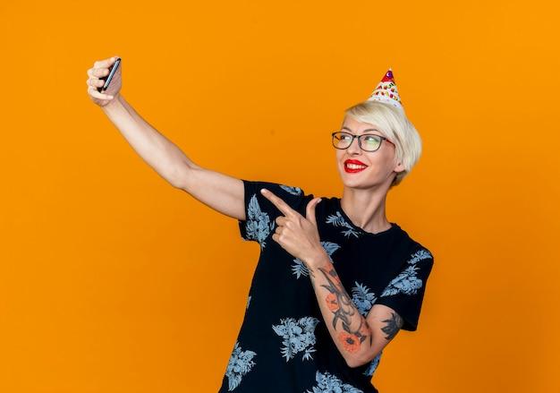 コピースペースでオレンジ色の背景に分離された電話を指してselfieを取っている眼鏡と誕生日の帽子を身に着けている若いブロンドのパーティーの女の子の笑顔