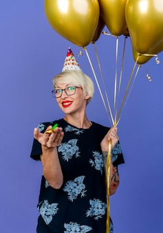 Smiling young blonde party girl wearing glasses and birthday cap holding balloons and party blower looking at camera isolated on purple background