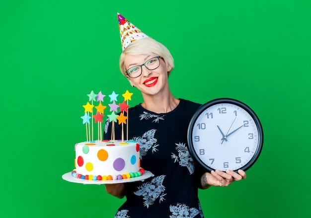 Sorridente ragazza bionda giovane partito con gli occhiali e cappello di compleanno tenendo la torta di compleanno e l'orologio che guarda l'obbiettivo isolato su priorità bassa verde con lo spazio della copia