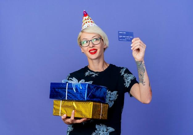 Sorridente ragazza bionda giovane partito con gli occhiali e berretto di compleanno che tiene scatole regalo e carta di credito guardando carta isolato su sfondo viola con spazio di copia