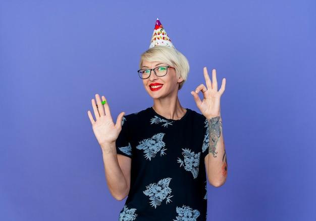 Sorridente ragazza bionda giovane partito con gli occhiali e cappello di compleanno tenendo il ventilatore del partito facendo segno ok guardando la telecamera isolata su sfondo viola con spazio di copia