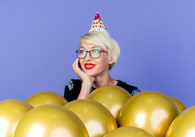 Sorridente ragazza bionda giovane partito con gli occhiali e cappello di compleanno in piedi dietro palloncini mettendo la mano sotto il mento guardando il lato isolato su sfondo viola