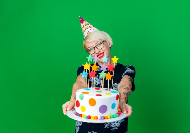 Smiling young blonde party girl wearing glasses and birthday cap stretching out birthday cake with stars looking at camera isolated on green background with copy space
