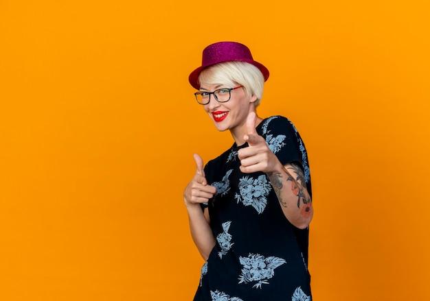 コピースペースでオレンジ色の背景に分離されたジェスチャーをしているカメラを見てパーティー帽子とメガネを身に着けている若いブロンドのパーティーの女の子を笑顔
