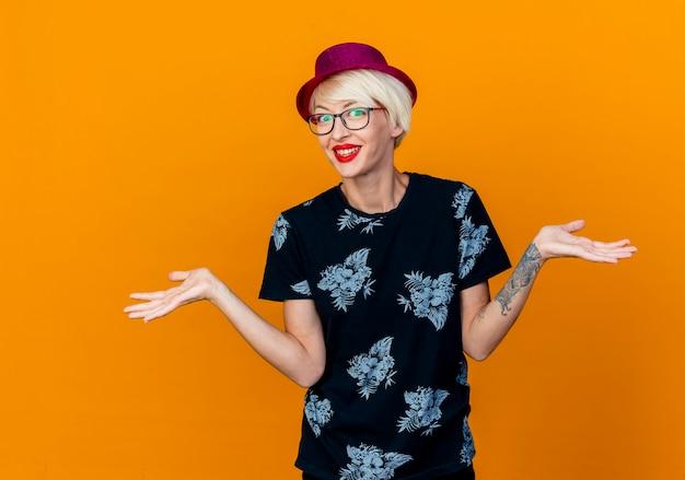 Sorridente giovane bionda party girl indossando il cappello del partito e occhiali che guarda l'obbiettivo che mostra le mani vuote isolate su sfondo arancione