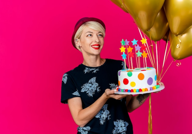 Smiling young blonde party girl wearing party hat holding balloons and birthday cake with stars looking at balloons isolated on crimson background with copy space
