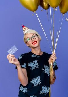 Sorridente giovane bionda festa donna con gli occhiali e berretto di compleanno che tiene palloncini e carta di credito guardando davanti isolato sulla parete viola