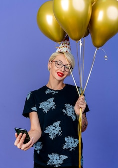 Smiling young blonde party woman wearing glasses and birthday cap holding balloons and mobile phone taking selfie isolated on purple wall