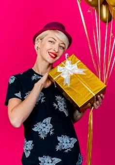 Sorridente giovane bionda festa donna che indossa il cappello del partito che tiene il contenitore di regalo e palloncini guardando davanti isolato sulla parete rosa
