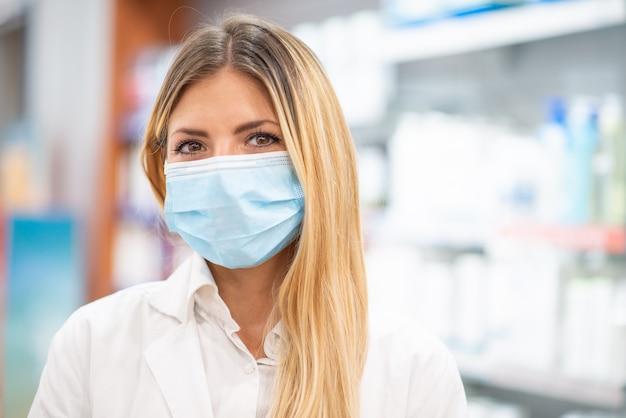 그녀의 약국 안에 코 비드 코로나 바이러스 마스크를 쓰고 웃는 젊은 금발 약사