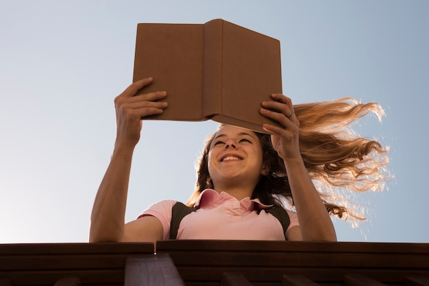 Smiling young blonde reading book in sunlight