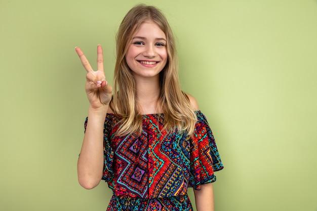 웃는 젊은 금발의 슬라브 소녀가 정면을 바라보며 승리의 표시를 하고 있다