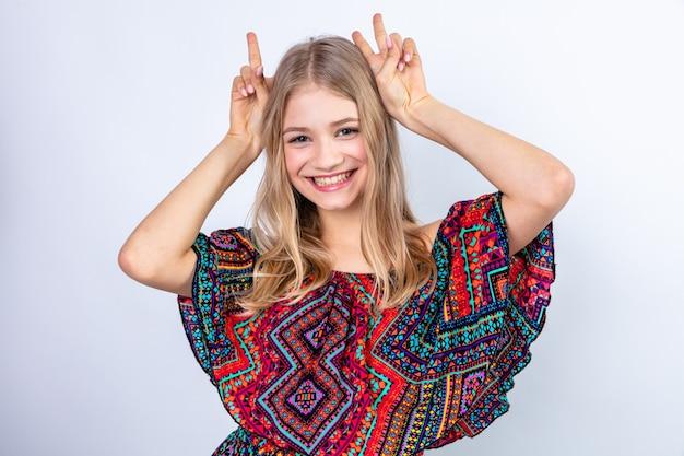 웃는 젊은 금발의 슬라브 소녀가 머리에 손을 얹고 손가락으로 뿔을 몸짓
