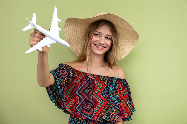 Smiling young blonde slavic girl with sun hat holding and looking at plane model