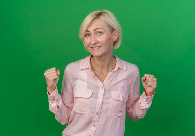 緑の背景に分離された拳を握り締め若い金髪のスラブ女性