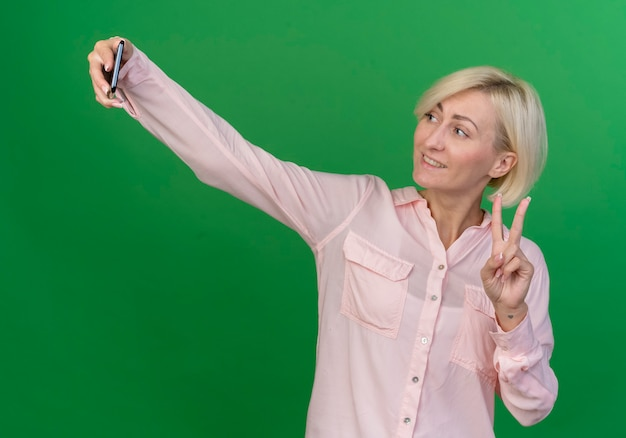 Smiling young blonde slavic woman doing peace sign and taking selfie isolated on green background