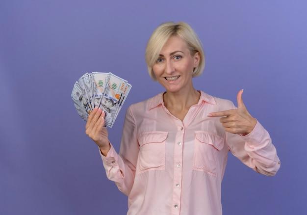 Улыбающаяся молодая блондинка славянская женщина, держащая и указывающая на деньги, изолированные на фиолетовом фоне