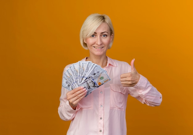 オレンジ色の壁に分離された彼女の親指を現金を保持している笑顔の若いブロンドのスラブ女性