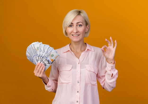 Smiling young blonde slavic woman holding cash and showing okey gesture isolated on orange wall