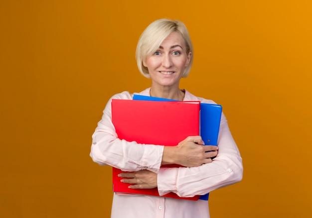 Sorridente giovane bionda donna slava che tiene le cartelle isolate sulla parete arancione
