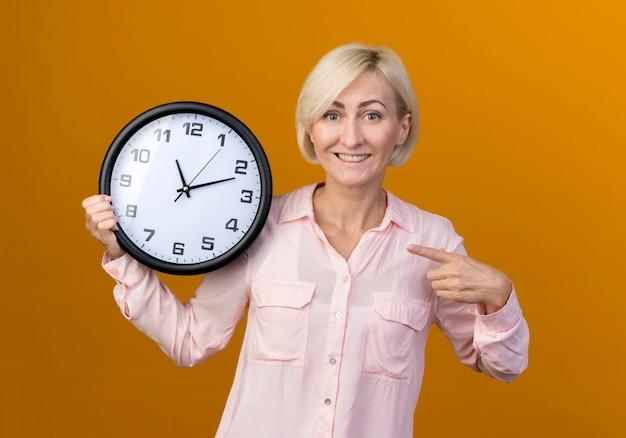 Sorridente giovane bionda donna slava azienda e punti all'orologio da parete isolato sull'arancio
