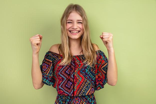 Sorridente giovane donna slava bionda che tiene i pugni alzati