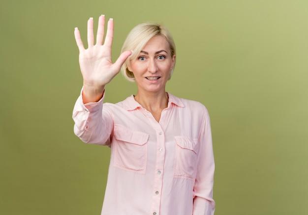 Sorridente giovane bionda donna slava che mostra cinque isolati sulla parete verde oliva