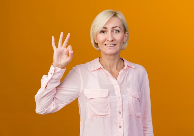 Sorridente giovane bionda donna slava che mostra okey gesto isolato sulla parete arancione