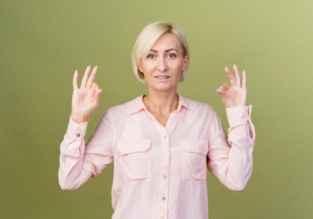 올리브 녹색 벽에 고립 된 평화 제스처를 보여주는 웃는 젊은 금발 슬라브 여자