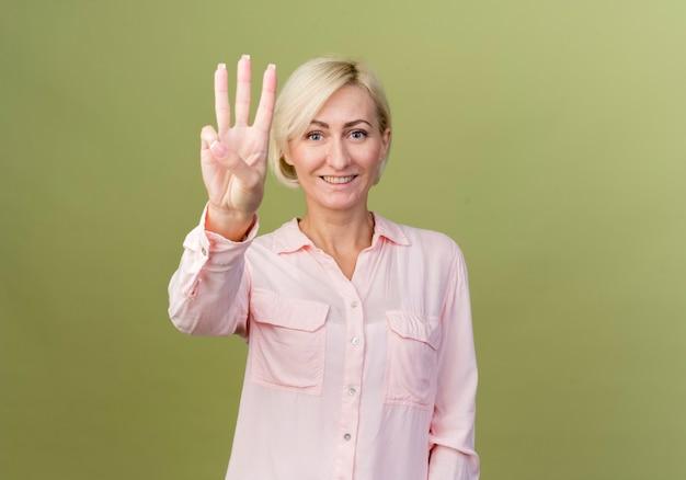 올리브 녹색 벽에 고립 된 3을 보여주는 웃는 젊은 금발 슬라브 여자