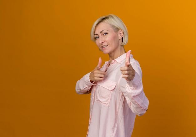 コピースペースでオレンジ色に分離されたジェスチャーを示す笑顔の若いブロンドのスラブ女性