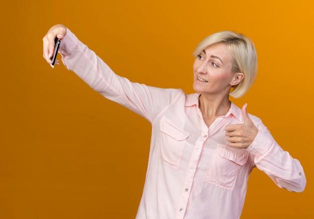 笑顔の若い金髪のスラブ女性は、オレンジ色に分離された彼女の親指を自分撮りを取ります