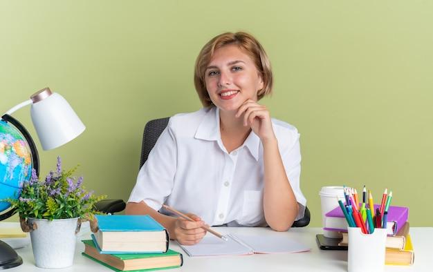 Sorridente giovane studentessa bionda seduta alla scrivania con gli strumenti della scuola che tengono la matita toccando il mento guardando la telecamera isolata sul muro verde oliva