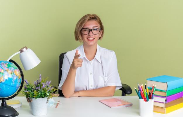 Sorridente giovane studentessa bionda con gli occhiali seduto alla scrivania con gli strumenti della scuola guardando e puntando la telecamera strizzando l'occhio isolata sul muro verde oliva