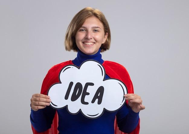 Sorridente giovane ragazza bionda del supereroe in mantello rosso che tiene bolla idea isolata sulla parete bianca con lo spazio della copia