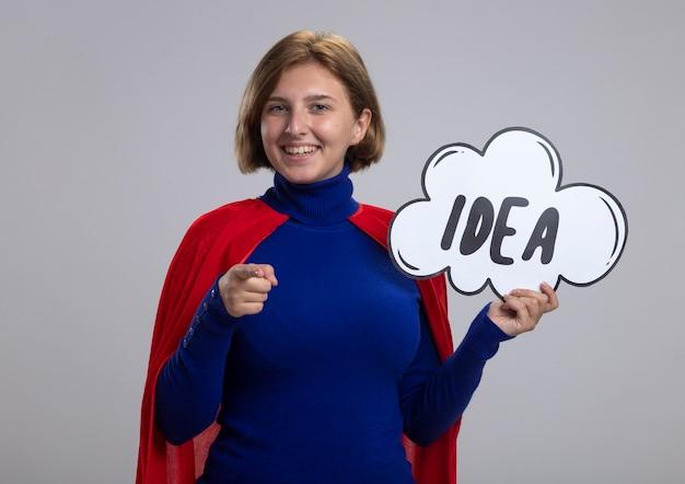Sorridente giovane ragazza bionda del supereroe in mantello rosso che tiene bolla idea guardando e indicando la fotocamera isolata su sfondo bianco