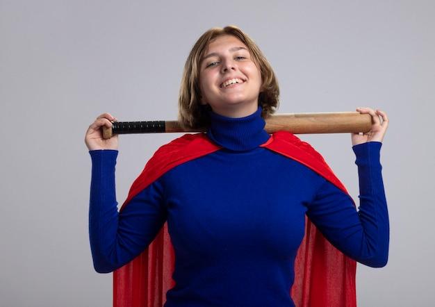 Улыбающаяся молодая белокурая женщина-супергерой в красном плаще держит бейсбольную биту за шеей, глядя на перед, изолированную на белой стене