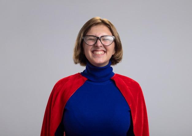 Улыбающаяся молодая белокурая женщина-супергерой в красном плаще в очках с закрытыми глазами изолирована на белой стене