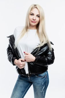 Smiling young blonde woman in black jacket and jeans. white wall. vertical.