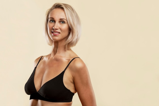 Smiling young blonde woman in black sports top.