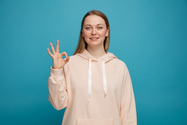 Okサインをしている若いブロンドの女性の笑顔