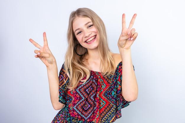 Sorridente giovane donna bionda gesticolando segno di vittoria