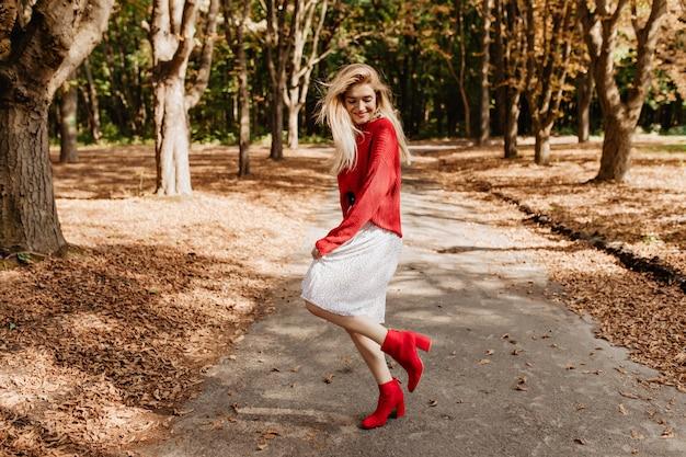 秋の公園で楽しんでいる笑顔の若いブロンドの女性。スタイリッシュな赤い靴と白いドレスで踊る。