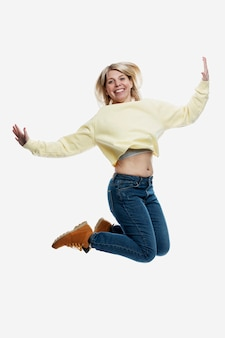Smiling young blonde woman in jeans and a yellow sweater is jumping. activity and positivity. isolated on white background. vertical.