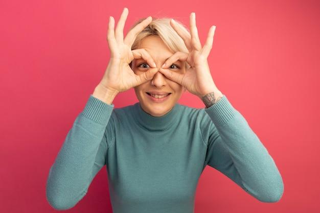 분홍색 벽에 격리된 쌍안경으로 손을 사용하여 표정 제스처를 하고 앞을 바라보고 있는 웃고 있는 젊은 금발 여성