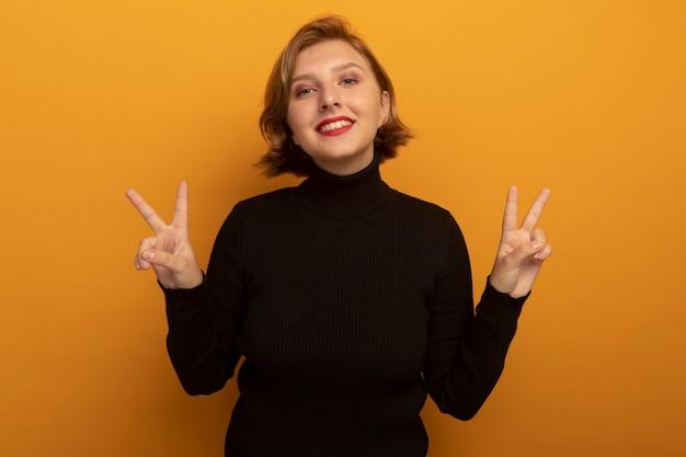 オレンジ色の壁に分離されたピースサインをやって正面を見て笑顔の若いブロンドの女性